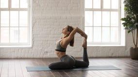 Yoga de pratique de femme, pose de Rajakapotasana, l'un Roi à jambes Pigeon photos libres de droits