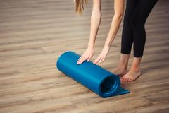 Yoga de pratique de femme, se préparant au tapis d'exercice, de déroulement ou de roulement de yoga image stock