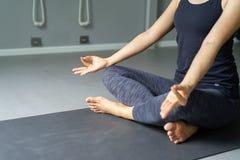 Yoga de pratique de jeune femme à l'arrière-plan gris Les jeunes font Photos libres de droits