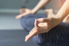 Yoga de pratique de jeune femme à l'arrière-plan gris Les jeunes font Photo stock