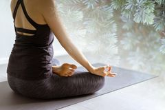 Yoga de pratique de jeune femme à l'arrière-plan gris Les jeunes font Image stock
