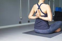Yoga de pratique de jeune femme avec le namaste derrière le dos fonctionnement Images stock