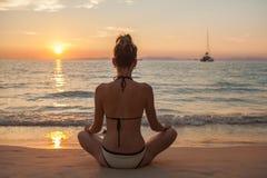 Yoga de pratique de jeune femme en bonne santé sur la plage au coucher du soleil photographie stock