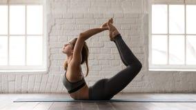 Yoga de pratique de jeune femme, faisant l'exercice de Dhanurasana, pose d'arc photographie stock