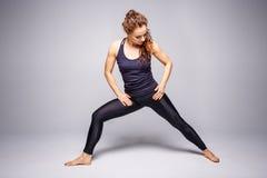 Yoga de pratique de jeune femme mince contre le mur gris Photographie stock libre de droits
