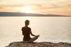 Yoga de pratique de jeune femme près de la mer au coucher du soleil Harmonie, méditation et concept de voyage Style de vie sain photographie stock