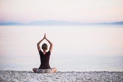Yoga de pratique de jeune femme près de la mer Concept d'harmonie et de méditation image stock