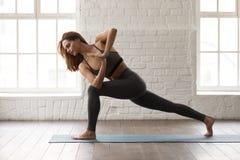 Yoga de pratique de jeune femme, se tenant dans la pose de Parsvakonasana, angle latéral images stock