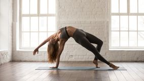 Yoga de pratique de jeune femme, se tenant dans la pose de Wild Thing, Camatkarasana image stock