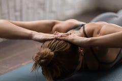 Yoga de pratique de jeune femme, visage menteur vers le bas, cou renforçant des exercices photos stock
