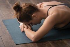 Yoga de pratique de jeune femme, visage menteur vers le bas, détendant après la formation photos stock
