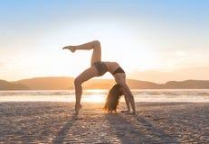Yoga de pratique de jeune fille sur la plage au coucher du soleil, beau bord de la mer de méditation de vacances d'été de femme Photo libre de droits