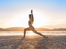 Yoga de pratique de jeune fille sur la plage au coucher du soleil, beau bord de la mer de méditation de vacances d'été de femme Photographie stock