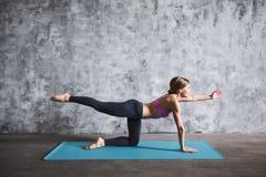 Yoga de pratique de sourire de belle femme, se reposant sur un tapis de yoga dans le gymnase images libres de droits