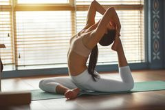Yoga de pratiques en matière de jeune femme au gymnase par la fenêtre images libres de droits