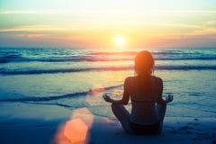Yoga de silhouette de femme sur la plage pendant le coucher du soleil passe-temps Images libres de droits