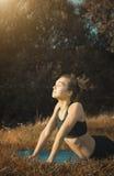 Yoga del entrenamiento de la mujer joven al aire libre imágenes de archivo libres de regalías