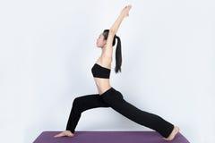 Yoga del entrenamiento de la mujer joven en el fondo blanco Foto de archivo libre de regalías