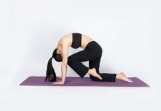 Yoga del entrenamiento de la mujer joven en el fondo blanco Fotos de archivo libres de regalías