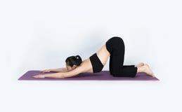 Yoga del entrenamiento de la mujer joven en el fondo blanco Imagen de archivo