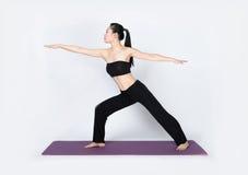 Yoga del entrenamiento de la mujer joven en el fondo blanco Foto de archivo