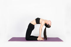 Yoga del entrenamiento de la mujer joven en el fondo blanco Imagen de archivo libre de regalías