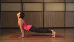 Yoga del entrenamiento de la mujer joven - perro ascendente de la cara almacen de metraje de vídeo