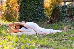 Yoga del socio de la pr?ctica del hombre joven y de la mujer al aire libre en el d?a de verano de madera fotografía de archivo libre de regalías