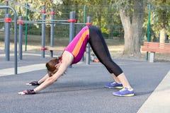 Yoga delgada magnífica de las prácticas de la mujer joven en el sportsground al aire libre Abajo de hacer frente a asana del perr fotos de archivo