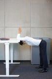 Yoga dell'ufficio - uomo di affari che si esercita all'alto scrittorio Immagini Stock