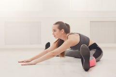 Yoga della donna che allunga a casa Immagine Stock