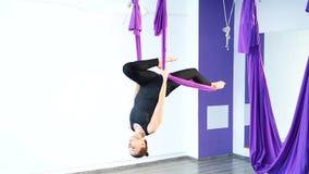 Yoga della mosca Giovane donna che pratica yoga antigravità aerea con un'amaca video d archivio