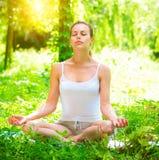 yoga Den unga kvinnan som gör yoga, övar utomhus royaltyfri fotografi