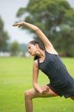 Yoga der jungen Frau, das in Park ausdehnt Lizenzfreies Stockfoto