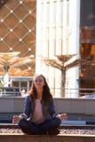 Yoga des jungen Mädchens und meditiert im Lotussitz in einer Großstadt lizenzfreie stockbilder