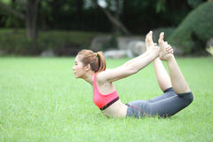 Yoga dhanurasana bow pose by asian woman on lawn Stock Photo