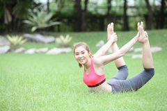 Yoga dhanurasana bow pose by asian woman on lawn Royalty Free Stock Photo