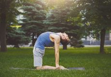 Yoga di addestramento dell'uomo nella posa del cammello all'aperto Fotografia Stock