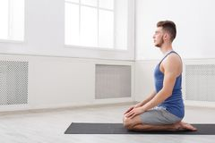 Yoga di addestramento dell'uomo nella posa dell'eroe, vista laterale Fotografia Stock Libera da Diritti