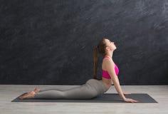 Yoga di addestramento della donna nella posa della cobra Immagini Stock