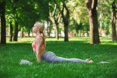 Yoga di addestramento della donna nella posa della cobra all'aperto Fotografia Stock