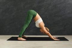 Yoga di addestramento della donna nella posa del cane in palestra Fotografie Stock