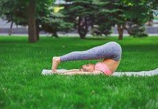 Yoga di addestramento della donna nella posa dell'aratro all'aperto Fotografia Stock