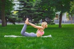 Yoga di addestramento della donna nella posa dell'arco all'aperto Immagini Stock