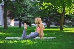 Yoga di addestramento della donna nella posa dell'arco all'aperto Immagine Stock