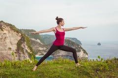 Yoga di addestramento della donna sulla scogliera vicino all'oceano Immagini Stock Libere da Diritti