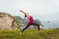 Yoga di addestramento della donna sulla scogliera vicino all'oceano Fotografia Stock