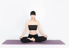 Yoga di addestramento della giovane donna su fondo bianco Fotografia Stock