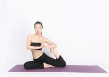 Yoga di addestramento della giovane donna su fondo bianco Immagine Stock