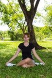 Yoga di esercizio delle giovani donne con fornito di gambe trasversale Fotografie Stock